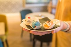 Κλείστε επάνω του θηλυκού χεριού που κρατούν το πιάτο με τα σπιτικά κέικ στο θόριο Στοκ φωτογραφία με δικαίωμα ελεύθερης χρήσης