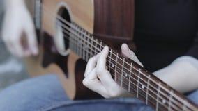 Κλείστε επάνω του κιθαρίστα που παίζει μια ακουστική κιθάρα φιλμ μικρού μήκους