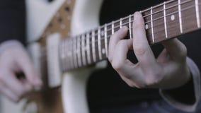 Κλείστε επάνω του κιθαρίστα που παίζει μια ηλεκτρική κιθάρα φιλμ μικρού μήκους