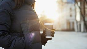 Κλείστε επάνω του κοριτσιού παραδίδει τα γάντια πίνοντας τον καφέ, ηλιόλουστος χειμώνας, φλόγα φακών από τον ήλιο απόθεμα βίντεο