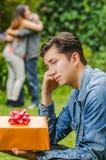 Κλείστε επάνω του λυπημένου ατόμου που φορά ένα σακάκι Jean και μαύρα εσώρουχα καθμένος στο έδαφος που κρατά ένα δώρο στα χέρια τ στοκ φωτογραφία με δικαίωμα ελεύθερης χρήσης