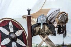 Κλείστε επάνω του μεσαιωνικού εξοπλισμού ιπποτών στην παλαιά σκηνή ύπνου Κράνος μετάλλων, ασπίδα, ξίφος στοκ εικόνα