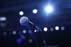 Κλείστε επάνω του μικροφώνου στη αίθουσα συναυλιών ή τη αίθουσα συνδιαλέξεων με τα κρύα φω'τα στο υπόβαθρο Στοκ εικόνα με δικαίωμα ελεύθερης χρήσης