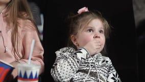 Κλείστε επάνω του μικρού κοριτσιού προσέχει έναν κινηματογράφο και τρώει popcorn φιλμ μικρού μήκους