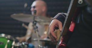 Κλείστε επάνω του μουσικού που μαδά με το χέρι τις σειρές κιθάρων απόθεμα βίντεο