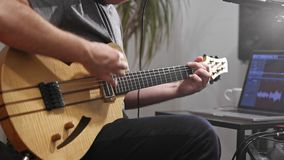 Κλείστε επάνω του μουσικού που παίζει την ηλεκτρική κιθάρα στο στούντιο εγχώριας μουσικής απόθεμα βίντεο