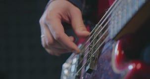 Κλείστε επάνω του μουσικού που παίζει τη βαθιά κιθάρα απόθεμα βίντεο