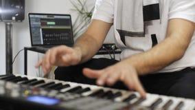 Κλείστε επάνω του μουσικού που παίζει το πληκτρολόγιο του Midi στο στούντιο εγχώριας μουσικής απόθεμα βίντεο
