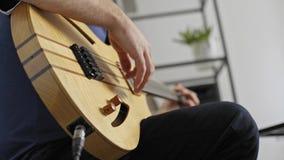 Κλείστε επάνω του μουσικού που συνδέει στην ηλεκτρική κιθάρα στο στούντιο εγχώριας μουσικής φιλμ μικρού μήκους