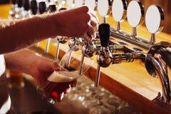 Κλείστε επάνω του μπάρμαν που χύνει τη σκοτεινή μπύρα στο γυαλί στοκ εικόνες