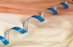 Κλείστε επάνω του μπλε στριμμένου μέτρου ταινιών σχετικά με την κρέμα και το μπεζ ύφασμα με την υφασματεμπορία Στοκ Εικόνες