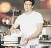 Κλείστε επάνω του νέου ελκυστικού ατόμου που λερώνει την άσπρη κρέμα στο κέικ σοκολάτας στοκ φωτογραφίες με δικαίωμα ελεύθερης χρήσης