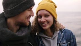 Κλείστε επάνω του νέου ευτυχούς ζεύγους hipster που στέκεται μαζί και που αγκαλιάζει στην παραλία Νέοι που φορούν τα θερμά ενδύμα απόθεμα βίντεο
