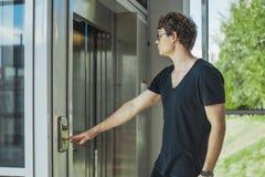 Κλείστε επάνω του νεαρού άνδρα που πιέζει το κουμπί του ανελκυστήρα στο σταθμό μετρό στοκ εικόνες