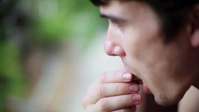 Κλείστε επάνω του νεαρού άνδρα τρώει salak ή φρούτα φιδιών σε ένα θολωμένο πράσινο υπόβαθρο 1920x1080 απόθεμα βίντεο