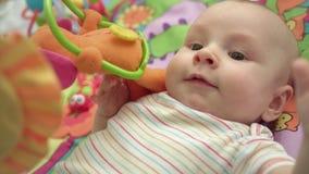 Κλείστε επάνω του νηπίου που παρουσιάζει γλώσσα Πορτρέτο του χαριτωμένου παιχνιδιού μωρών με τα παιχνίδια απόθεμα βίντεο
