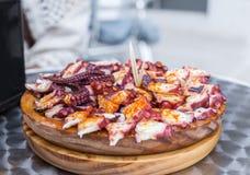 Κλείστε επάνω του νόστιμου ξύλινου πιάτου του της Γαλικίας μαγειρευμένου ύφος χταποδιού με το ελαιόλαδο πάπρικας και gallega pulp Στοκ εικόνες με δικαίωμα ελεύθερης χρήσης