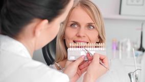 Κλείστε επάνω του οδοντιάτρου που επιλέγει τα δόντια χρώματος από την παλέτα απόθεμα βίντεο