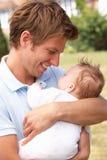 Κλείστε επάνω του πατέρα που αγκαλιάζει το νεογέννητο αγοράκι Outdo Στοκ Φωτογραφία