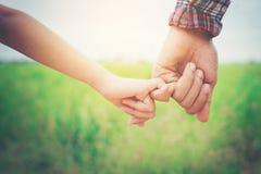Κλείστε επάνω του πατέρα που κρατά το χέρι κορών του, τόσο γλυκός, οικογενειακό Tj στοκ φωτογραφία με δικαίωμα ελεύθερης χρήσης