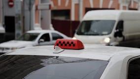 Κλείστε επάνω του πορτοκαλιού σημαδιού στεγών ταξί με τους ελεγκτές στο υπόβαθρο των αυτοκινήτων απόθεμα βίντεο