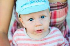 Κλείστε επάνω του προσώπου αγοράκι με τα μπλε μάτια με το ανοικτό στόμα και την μπλε ΚΑΠ Συγκινήσεις παιδιών και παιδιών Στοκ Φωτογραφίες