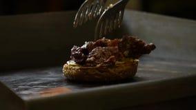 Κλείστε επάνω του προϊσταμένου βάζει το κρέας και τηγανίζει burger Οι ροές χυμού από το κρέας Ο μάγειρας μαγειρεύει απόθεμα βίντεο