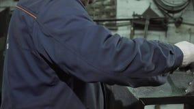 Κλείστε επάνω του σιδηρουργού στη προστατευτική ενδυμασία χρησιμοποιώντας τα εργαλεία και μια μηχανή συγκόλλησης φιλμ μικρού μήκους