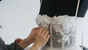 Κλείστε επάνω του σχεδιαστή μόδας για τις νύφες στη δαντέλλα βελόνων καρφιτσών στούντιό του και τα λουλούδια στο γαμήλιο φόρεμα S απόθεμα βίντεο