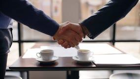 Κλείστε επάνω του τινάγματος δύο επιχειρηματιών παραδίδει τον καφέ μετά από τις διαπραγματεύσεις απόθεμα βίντεο