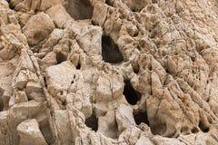 Κλείστε επάνω του τοίχου βράχου ερήμων με τις βαθιές σκοτεινές τρύπες και τις ρωγμές στην επιφάνεια στοκ εικόνες