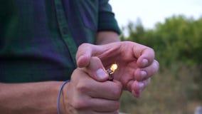 Κλείστε επάνω του φωτός χεριών προσώπων ` s την πυρκαγιά στον αναπτήρα Η φωτεινή ελαφρύτερη φλόγα σε σε αργή κίνηση απόθεμα βίντεο