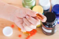 Κλείστε επάνω του χεριού κρατά ένα συμπλήρωμα βιταμινών στοκ φωτογραφία με δικαίωμα ελεύθερης χρήσης