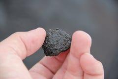 Κλείστε επάνω του χεριού κρατώντας τον ιριδίζοντα βράχο λάβας Στοκ Εικόνες