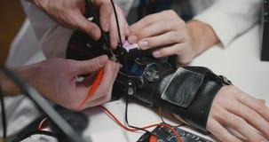 Κλείστε επάνω του χεριού μηχανικών που μετρά την τάση του κινητικού γαντιού φιλμ μικρού μήκους
