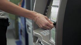 Κλείστε επάνω του χεριού μιας γυναίκας χρησιμοποιώντας την τραπεζική μηχανή, απόσυρση του ATM με την επιχείρηση πιστωτικών καρτών απόθεμα βίντεο