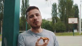 Κλείστε επάνω του όμορφου ατόμου που τρώει την πίτσα σε ένα γήπεδο μπάσκετ απόθεμα βίντεο