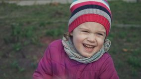 Κλείστε επάνω του όμορφου καυκάσιου μικρού κοριτσιού με τα όμορφα μπλε μάτια που φορούν το ριγωτό χαμόγελο καπέλων παιδική ηλικία απόθεμα βίντεο