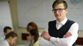 Κλείστε επάνω του όμορφου νέου εργαζομένου που φορά eyeglasses και το πουκάμισο φανέλας στο μικρό γραφείο με άλλο προσωπικό στο υ φιλμ μικρού μήκους