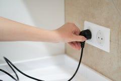 Κλείστε επάνω το ένθετο χεριών γυναικών ή βγάλτε το βούλωμα elecrticity στην έξοδο στον τοίχο στοκ εικόνα με δικαίωμα ελεύθερης χρήσης