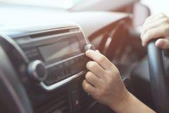 Κλείστε επάνω το ανοικτό άκουσμα ραδιοφώνων αυτοκινήτου χεριών Μεταβαλλόμενοι ραδιοσταθμοί κουμπιών στροφής οδηγών αυτοκινήτων στοκ φωτογραφία