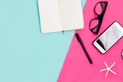 Κλείστε επάνω το γραφείο γραφείων με τα χαρτικά, τα γυαλιά και το smartphone στοκ φωτογραφίες
