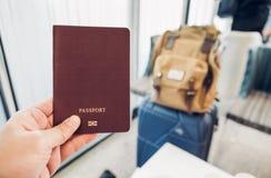 Κλείστε επάνω το διαβατήριο εκμετάλλευσης χεριών στο τερματικό αερολιμένων με τη βαλίτσα Στοκ φωτογραφία με δικαίωμα ελεύθερης χρήσης
