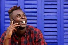 Κλείστε επάνω το εύθυμο afro Αμερικανός μπορεί να επανδρώσει την ομιλία στο τηλέφωνο κυττάρων και το κοίταγμα μακριά Στοκ εικόνες με δικαίωμα ελεύθερης χρήσης
