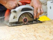 Κλείστε επάνω το ηλεκτρικό πριόνι να πριονίσει τον ξύλινο πίνακα στοκ φωτογραφίες