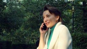 Κλείστε επάνω το θηλυκό με την κοντή τρίχα που μιλά και που χαμογελά το κινητό τηλέφωνο στο πάρκο φιλμ μικρού μήκους