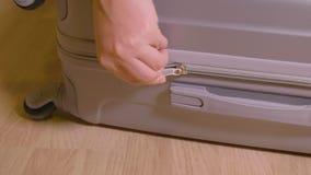 Κλείστε επάνω το θηλυκό σύνδεσμο φερμουάρ χεριών κλείνοντας στη βαλίτσα ταξιδιού στο ξύλινο πάτωμα φιλμ μικρού μήκους