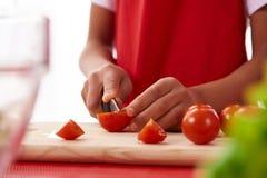 κλείστε επάνω Το κορίτσι αφροαμερικάνων τεμαχίζει τις ντομάτες στοκ εικόνες
