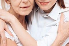κλείστε επάνω Το κορίτσι περιποιείται την ηλικιωμένη γυναίκα στο σπίτι Αγκαλιάζουν ο ένας τον άλλον στοκ εικόνες