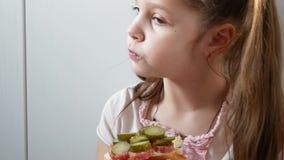 Κλείστε επάνω το κορίτσι που τρώει το σάντουιτς στην κουζίνα απόθεμα βίντεο